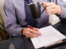 Businessman signing papers. And drinking coffee at the same time stock photography