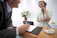Businessman signing at reception by receptionist on telephone Royalty Free Stock Photos