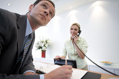 Businessman signing at reception by receptionist on telephone Stock Images