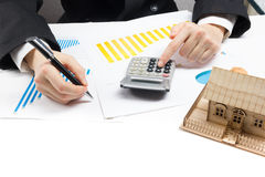 Businessman signs contract behind home architectural model Royalty Free Stock Images