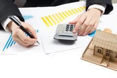 Businessman signs contract behind home architectural model Royalty Free Stock Photo