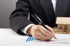 Businessman signs contract behind home architectural model Stock Photos
