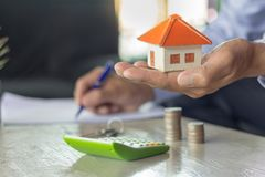 Businessman signs contract behind home architectural model. Home trading ideas stock photos