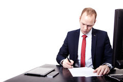 Businessman signs a contract in the workplace. Royalty Free Stock Image