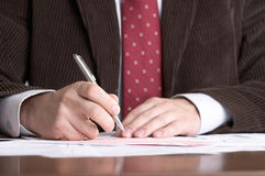 Businessman signs documents Royalty Free Stock Photo