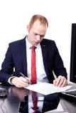Businessman signs documents in the workplace. Stock Images