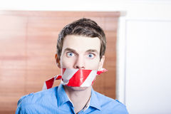 Businessman in silence with red warning tape Royalty Free Stock Image