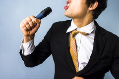 Businessman singing karaoke. Businessman with his tie loosened is singing karaoke Stock Images