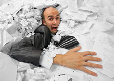 Businessman sinking in heap of documents. Businessman sinking in heap of documants and asking for help Royalty Free Stock Image