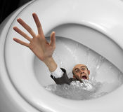 Businessman sinking in toilet bowl Royalty Free Stock Photography