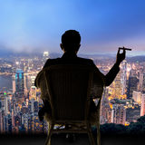 Businessman sit on chair. Silhouette of businessman sit on chair and hold a cigar, looking the harbor of Victoria at Hong Kong, Asia Royalty Free Stock Image