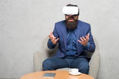Businessman sit chair wear hmd explore virtual reality or ar. Business partner interact in virtual reality. New. Opportunity. Business implement modern stock photography