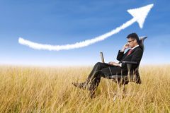 Businessman sit outdoor with success arrow sign Stock Images