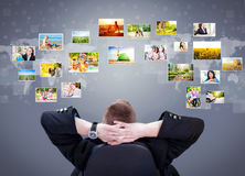 Businessman siting and looking at photo gallery images Stock Images