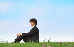 Businessman sits on grass, view in profile Royalty Free Stock Photos