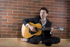 Businessman sits singing with guitar on the floor Royalty Free Stock Photos