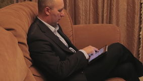 Businessman sits on a sofa and opens tablet. stock video