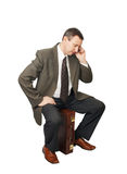 Businessman sits on suitcase and talks by phone Stock Photography