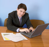Businessman sits at table with the laptop Royalty Free Stock Images