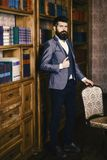 Businessman sits in vintage interior, holds book and cup of tea. Bearded man in luxury suit in his cabinet. Mature man. With calm face enjoys reading. Luxury stock images