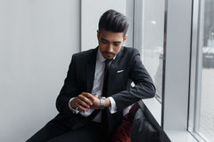 Businessman sits about window and looking at his watch. Royalty Free Stock Photography