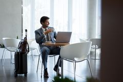 Businessman sitting in airport waiting area. Man with suitcase sitting in airport waiting area. Business man sitting at airport lounge with laptop having coffee Stock Photo