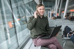 Businessman sitting at the airport working on a laptop and looking at the smartphone. royalty free stock photos