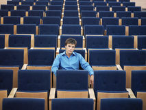 Businessman Sitting Alone On In Auditorium. Portrait of young businessman sitting alone in auditorium stock images