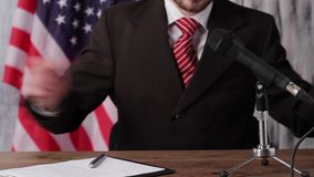 Businessman sitting beside american flag. Man speaks into microphone. People need answers. Honesty is always valued stock footage