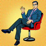 Businessman sitting in an armchair gesture okay Stock Images