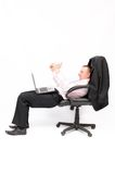 Businessman sitting in an armchair with a laptop. Stock Images