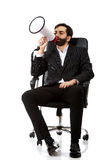 Businessman sitting on armchair with megaphone. Stock Photo