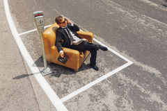 Businessman sitting on armchair in the middle of the road Stock Image