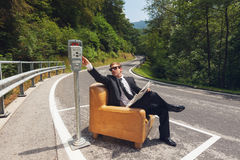 Businessman sitting on armchair in the middle of the road Stock Photos