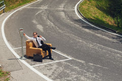 Businessman sitting on armchair in the middle of the road Stock Images