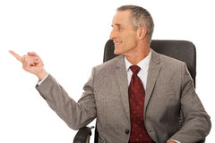 Businessman sitting on armchair and pointing left Stock Photos
