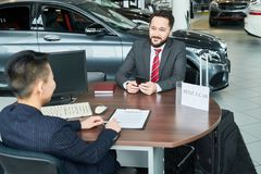 Rent a car. Businessman sitting at auto salon. He wants to rent a car royalty free stock photography