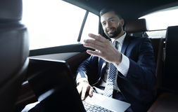 Businessman sitting in the back seat in the car and pointing his finger forward. Businessman points with his finger forward sitting in the back seat in the car Stock Photography