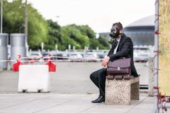Businessman sitting on a banch with briefcase wearing a gas mask on face. Businessman sitting on a banch with briefcase wearing a gas mask Stock Images