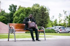 Businessman sitting on a banch wearing a gas mask with a briefcase. Businessman sitting on a banch wearing a gas mask looking in the briefcase Royalty Free Stock Photos