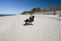 Businessman sitting on beach Stock Images