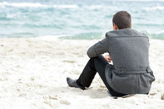 Businessman sitting on the beach alone Royalty Free Stock Images