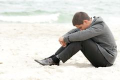 Businessman sitting on the beach alone Stock Photo
