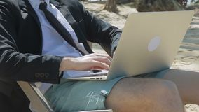 Businessman is sitting on the beach with laptop on his knees. stock video footage