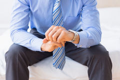 Businessman sitting on bed checking the time Royalty Free Stock Photos
