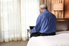 Businessman sitting on the bed in his hotel room using his laptop royalty free stock photography