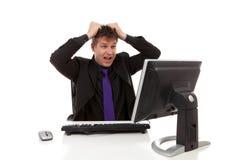 Businessman sitting behind desk is in despair Stock Photo
