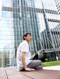 Businessman sitting on a bench. In front of an office building Royalty Free Stock Photo