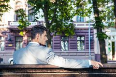 Businessman sitting on the bench. Back view portrait of a handsome businessman sitting on the bench outdoors Royalty Free Stock Photography