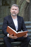 Businessman sitting on a bench. With a book Royalty Free Stock Images